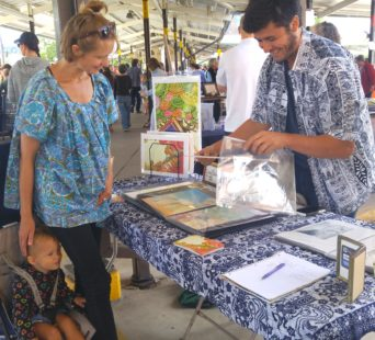 At the Kerrytown Bookfest, author and illustrator Robb N. Johnston, 32, right, signs his artwork, some of which is featured in his independently published picture books, for customer Tanja Baumann, 38, PHOTO/SHANA BOSLEY