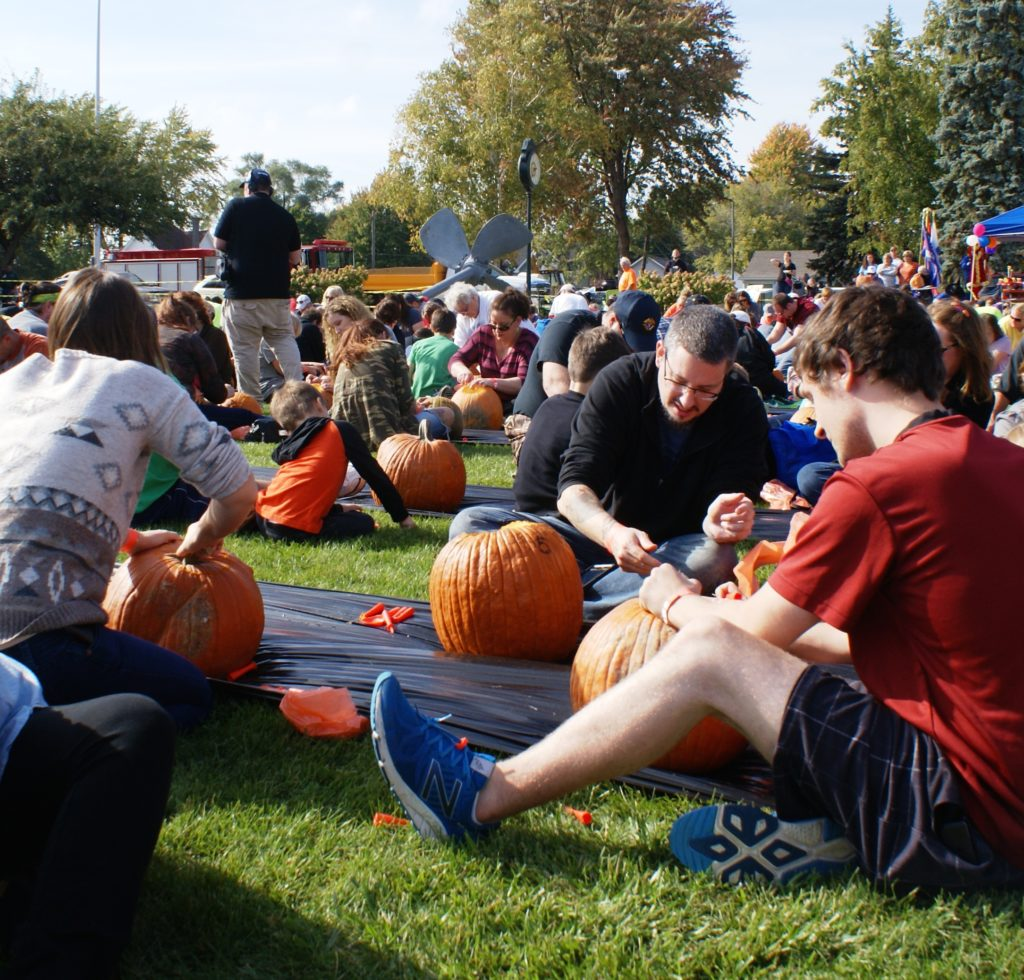 The rules required at least five minutes of simultaneous pumpkin carving, during which 738 people sat on the grass and worked on their pumpkins as a drone flew overhead, documenting the record attempt. PHOTO/COLLEEN KOWALEWSKI