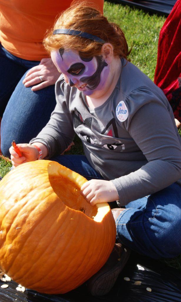Erin Wilson, 8, carves her contribution to the record attempt. Face painting, a costume contest, and trick-or-treating at local businesses made the event popular with local families. PHOTO/COLLEEN KOWALEWSKI