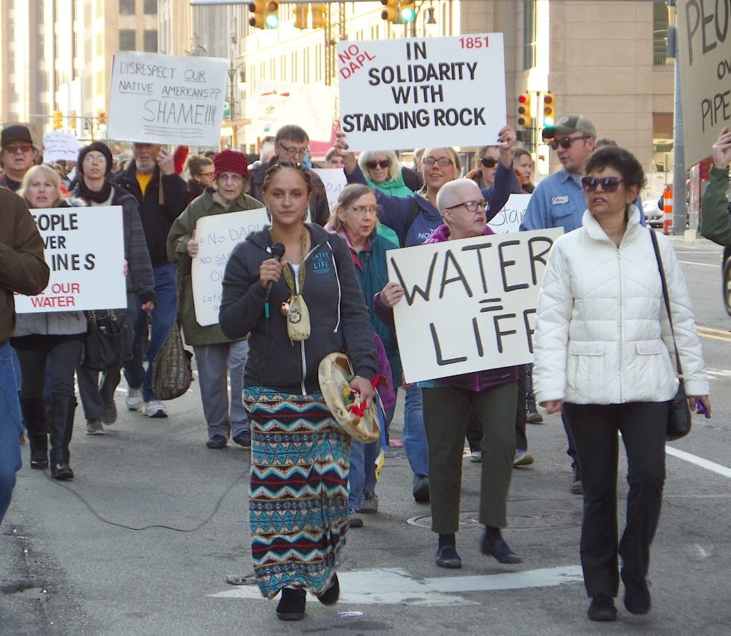 "Kayla Harris, founder of the Wayne State Native American Student Organization, led protesters in a chant of ""Water is life"" as they marched down Michigan Avenue in Detroit. The march and rally in Campus Martius Park were part of a national day of action in solidarity with the indigenous protesters at Standing Rock, North Dakota. PHOTO/COLLEEN KOWALEWSKI"